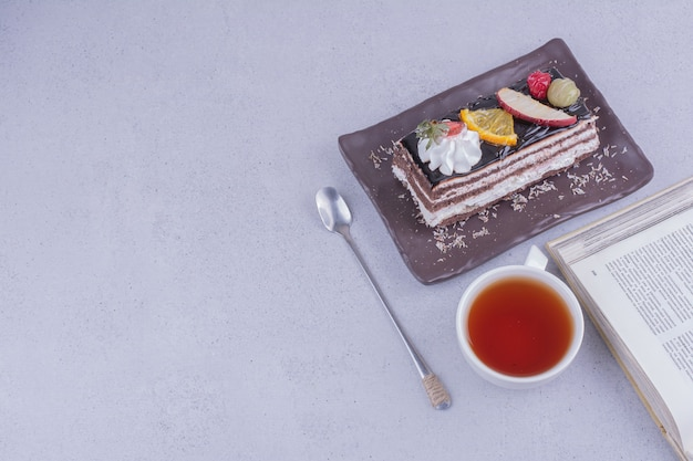 A slice of chocolate crepe cake with a cup of tea and fruits