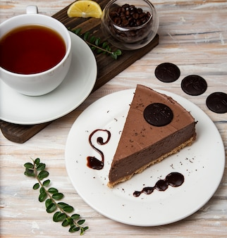 A slice of chocolate mousse cheesecake with chocolate chips and a cup of tea.