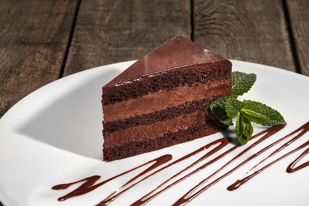 Slice of chocolate sponge cake with buttercream and chocolate ganache