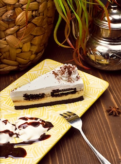 Slice of chocolate vanilla cheesecake on plate against a rustic brown wood table