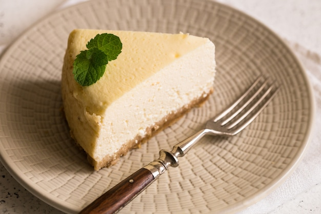 Slice of classical new york cheesecake on white plate. closeup view. home bakery