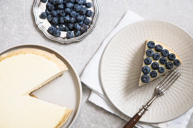 Slice of classical new york cheesecake with blueberries on white plate.