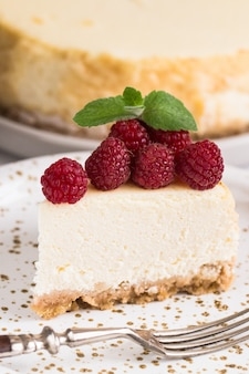 Slice of classical new york cheesecake with raspberries on white plate. closeup view. home bakery