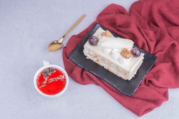 A slice of coconut cake with grape and walnut served with a cup of herbal tea