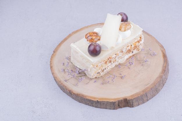Una fetta di torta al cocco con uva e noci su una tavola di legno