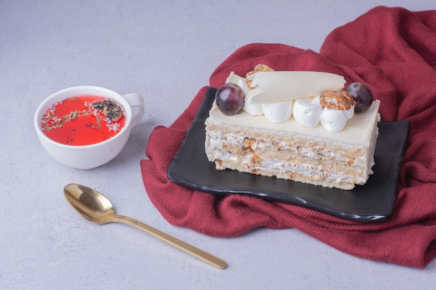 A slice of coconut cake with nuts and berries served with a cup of red drink