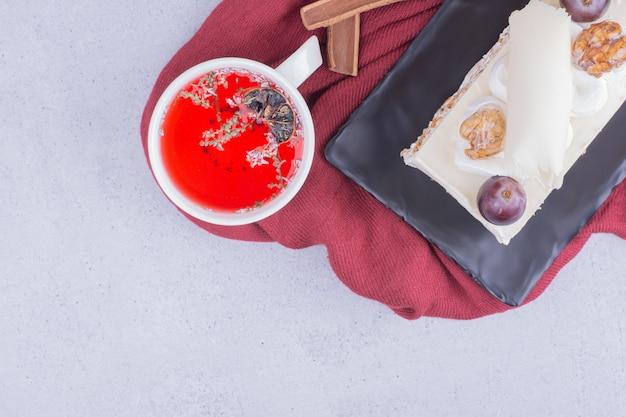 Una fetta di torta al cocco con noci e frutti di bosco servita con una tazza di bevanda rossa