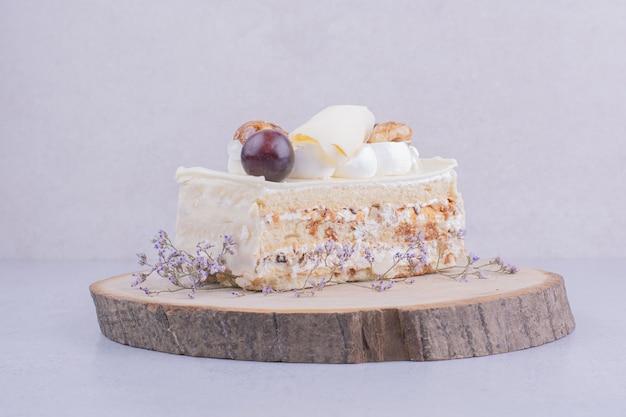 Una fetta di torta al cocco con noci e frutti di bosco
