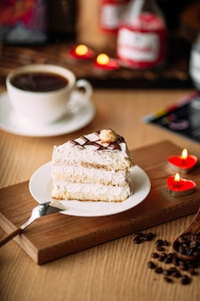 Slice creamy cake on decorated table with coffee