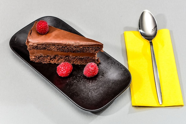 Slice of a delicious cake on a black plate