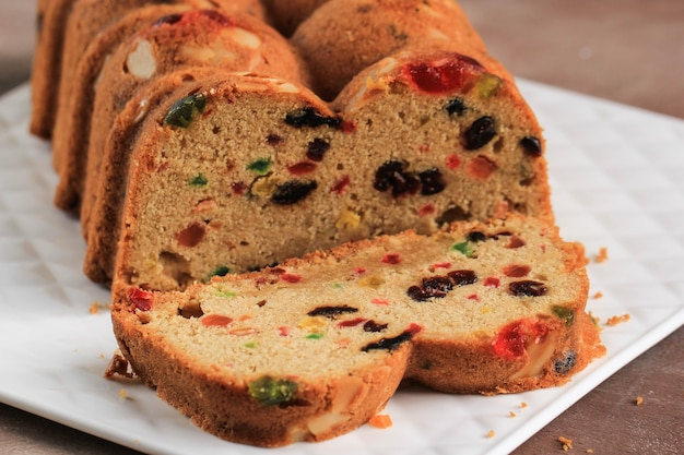 Slice of delicious homemade english fruit cake loaf pudding with dried mixed fruit, sultanas, raisins, and chopped almond. served during christmas party or new year eve
