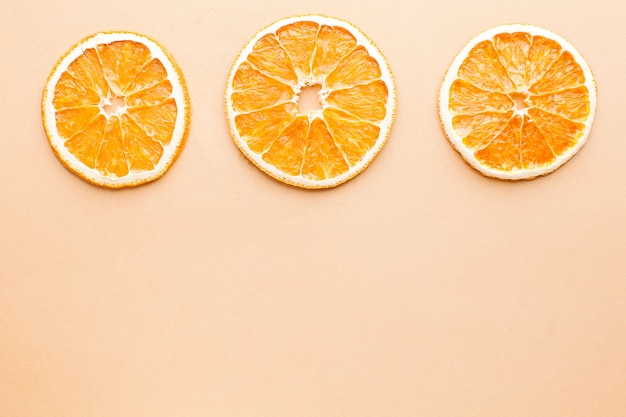 Slice of dried orange on a light brown background with space for text. minimalism, food concept.