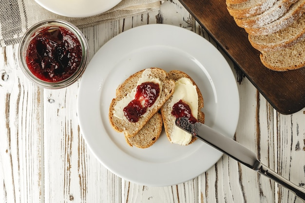 Slice of fresh bread with butter and jam on wooden table
