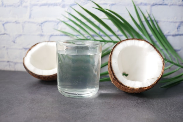 Slice of fresh coconut and glass of coconut water on table