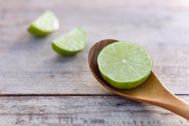 Slice of fresh limes on wood spoon and table