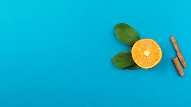 Slice of fresh orange near cinnamon and foliage