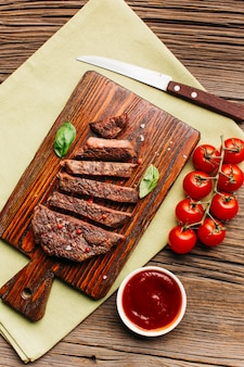 Slice of fried steak with red tomato sauce on wooden cutting board