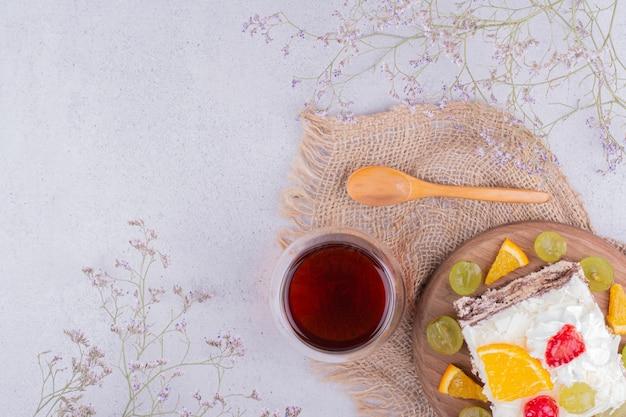 Una fetta di torta alla frutta con panna montata e tè