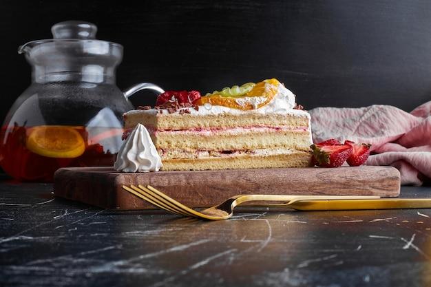 Una fetta di torta alla frutta sul piatto di legno.