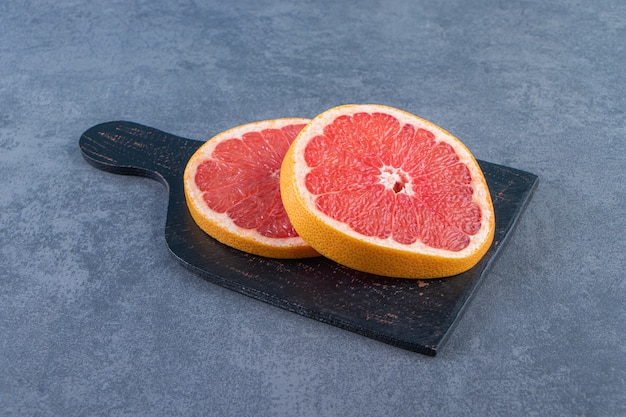 Slice grapefruit on a cutting board , on the marble background.