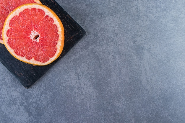 まな板の上で、大理石の背景にグレープフルーツをスライスします。
