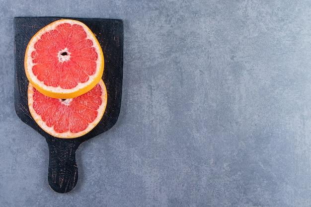 Нарезать грейпфрут на разделочной доске на мраморной поверхности.