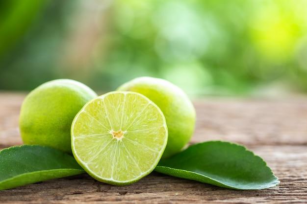 木製のテーブルの背景に緑の新鮮なレモンをスライス