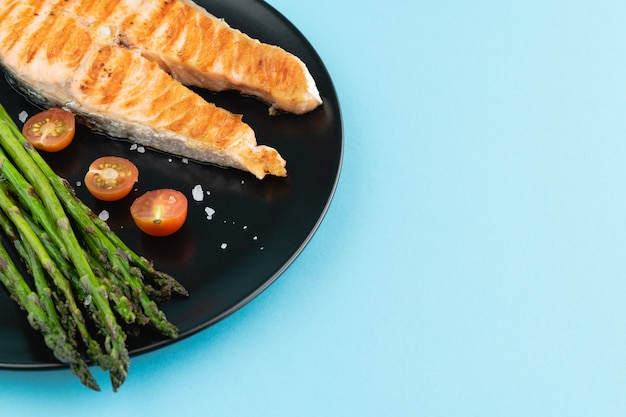 Slice of grilled salmon with green asparagus on black plate on blue surface. copy space.