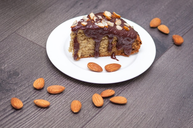 Slice of homemade banana bread with chocolate, almond  on wood