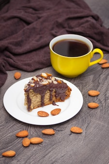 Slice of homemade banana bread with chocolate, almond and yellow cup of coffee on wood
