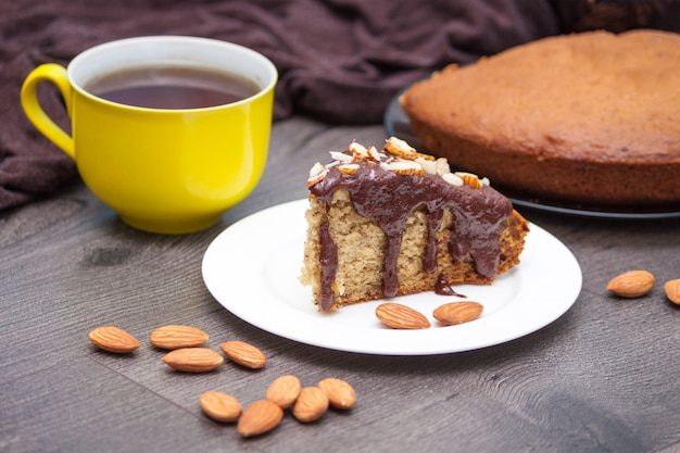 Slice of homemade banana bread with chocolate, almond and yellow cup of tea or coffee on wood