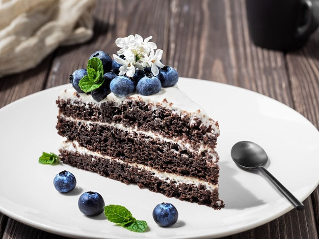 Slice of homemade bird cherry cake with sour cream, decorated with blueberries and mint leaves on a plate