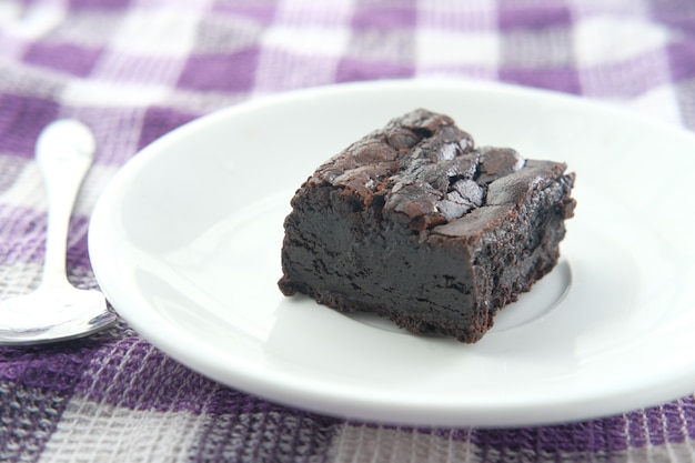Slice of homemade brownie on plate on table