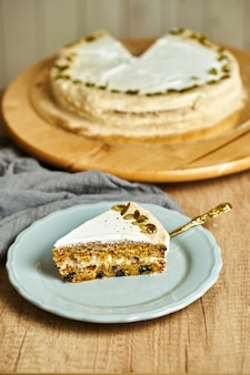 Slice of homemade carrot cake on plate. wooden background