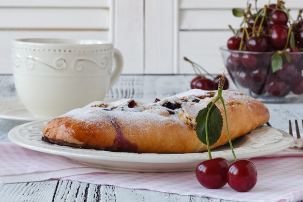 Slice of homemade cherry pie, cup of coffee, bowl with cherries