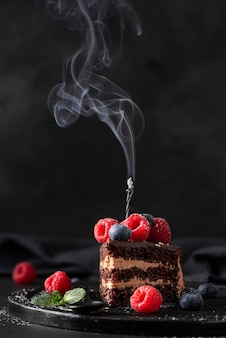 Slice of homemade chocolate cake with fresh berries and birthday candle, close-up