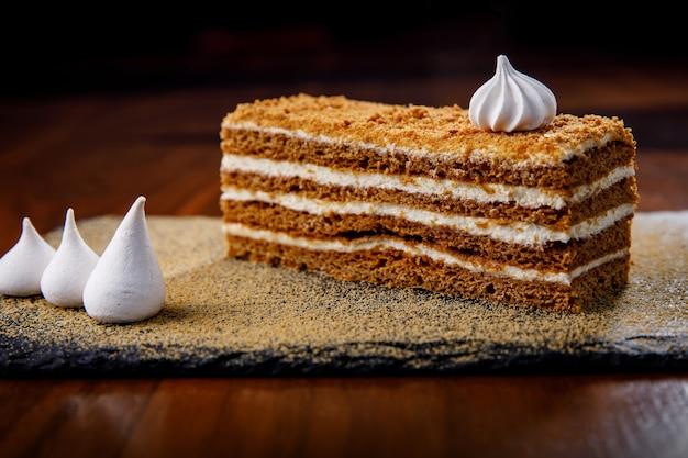 Slice of honey cake on a dark tray.