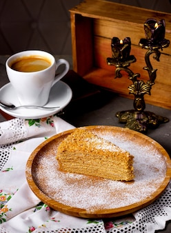A slice of honey cake served on bamboo plate