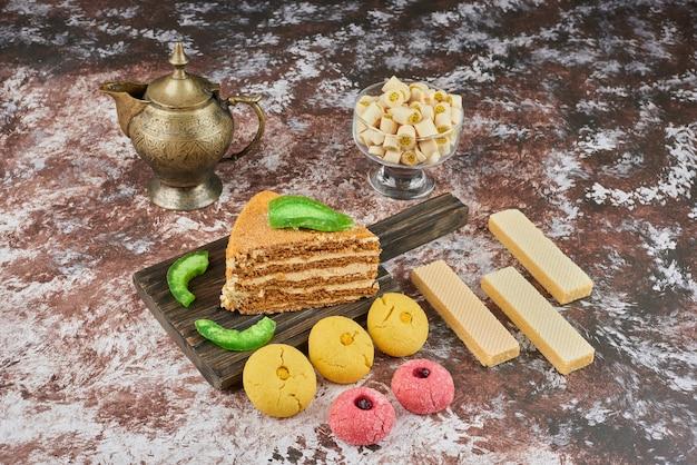 Una fetta di torta al miele con biscotti al burro e waffle.