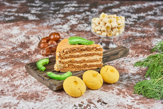 A slice of honey cake with butter cookies.