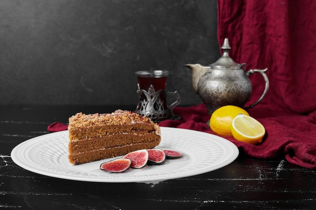A slice of honey cake with figs and tea.