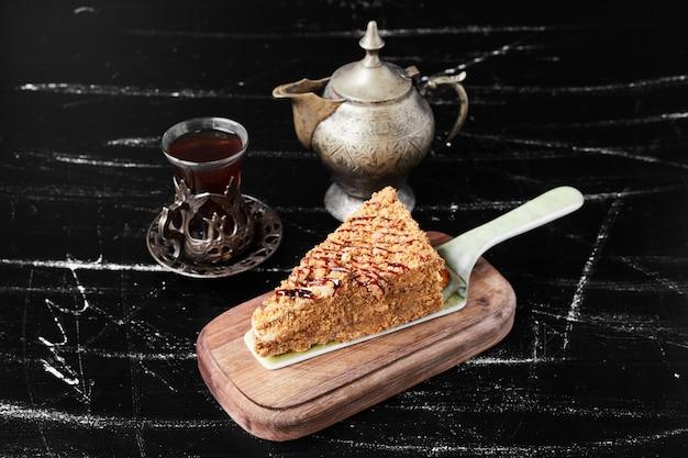Una fetta di torta al miele con un bicchiere di tè.