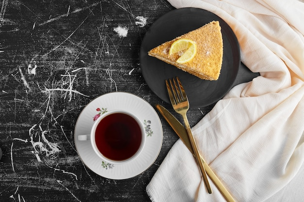 Una fetta di torta al miele al limone con una tazza di tè.