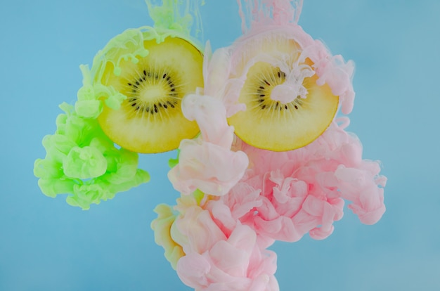 Slice kiwi fruits with partial focus of dissolving pink and green poster color in water.