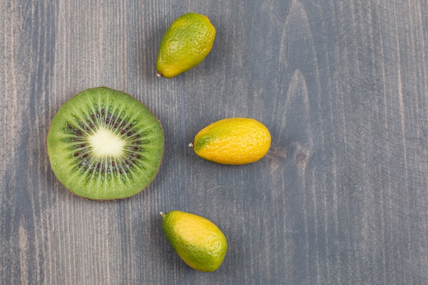 Slice of kiwi with small mandarins on marble surface