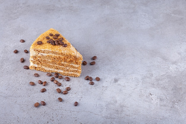 Fetta di torta al miele a strati con chicchi di caffè posto su uno sfondo di pietra.