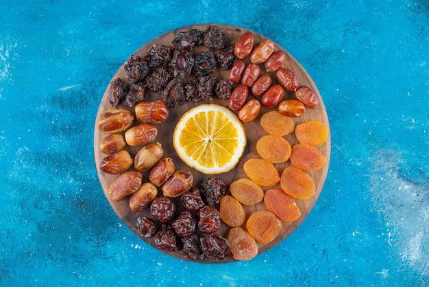 青い表面のボードにレモンとドライフルーツをスライスします