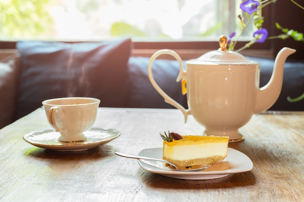 Slice of lemon cheesecake with cup of tea with flowers.