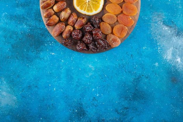 Affettare il limone e la frutta secca su un tagliere, sul tavolo blu.