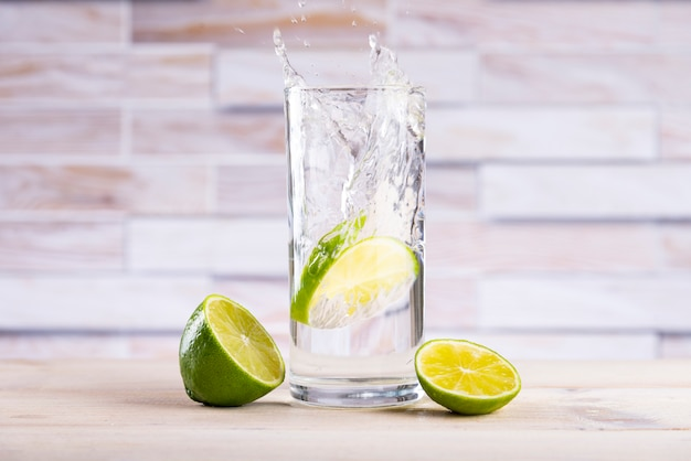 A slice of lemon falls into a glass with water, splashes fly on a wooden table